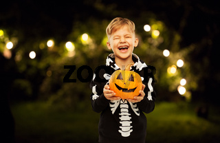 happy boy in halloween costume with jack-o-lantern