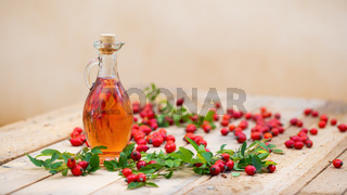 Rosehip oil in bottle laid on wooden palette with copy space
