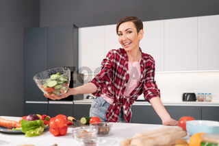 Happy holding bawl of salad young housewife cut tomato, cucumber, pepper for a family dinner or girls night standing in the kitchen. Healthy food living. Healthy lifestyle