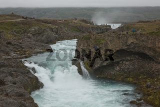 Tourists at The Godafoss (Icelandic: waterfall of the gods) which is a famous waterfall in Iceland. The breathtaking landscape of Godafoss waterfall attracts tourist to visit the Northeastern Region of Iceland
