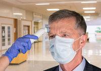 Senior man wearing face mask having temperature taken to check for virus at hospital