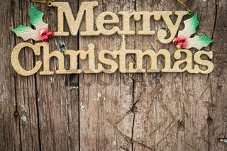 Gold text 'Merry Christmas' on wood