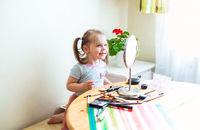Cute girl applying makeup at home