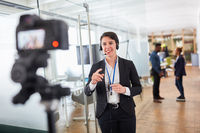 Business Frau als live Reporter vor der Video Kamera