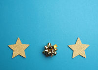 Christmas background with golden stars and bow on blue