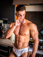 Handsome shirtless bodybuilder drinking water in kitchen