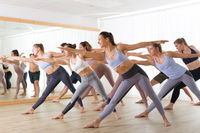 Group of young authentic sporty attractive people in yoga studio, practicing yoga lesson with instructor. Healthy active lifestyle, working out in gym