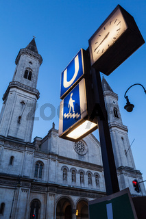 U-Bahn sign and St. Ludwig's Church (Ludwigskirche) in the evening.  Car Light Traces motion blur because of long exposure. Munich