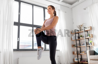 smiling young woman stretching leg at home