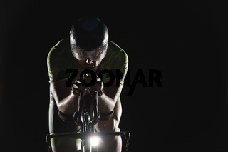triathlon athlete riding bike fast  at night