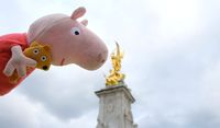 Peppa Pig doll looking at Ornate Queen Victoria Memorial in front of Buckingham Palace, London, england