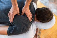 Sports physiotherapist massaging muscular strong man