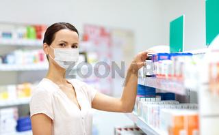 female customer in mask choosing drugs at pharmacy