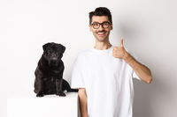 Image of dog owner and cute black pug looking at camera, man showing thumb-up in approval, recommending something, standing over white background