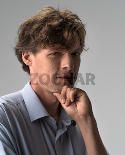 Thoughtful guy leaning hand, rubbing beard while thinking over difficult choice, indoor studio shot isolated on white or light grey background. Facial expressions, emotions, feelings