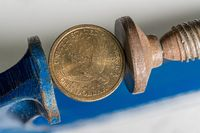 USA one dollar coin being squeezed between the solid jaws of a vise or vice