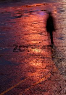 Person walking alone in the dark under bright orange light after rain.