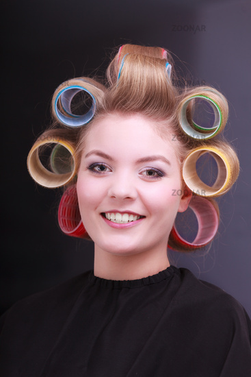 Happy blond girl hair curlers rollers by hairdresser in beauty salon