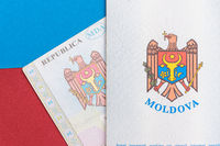Republic of Moldova concept. The Moldovan passport on a blue and red background. Coloseup of the emblem/coat of arms of Moldova. Moldova Finance and economy concept