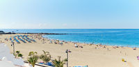 Tenerife, Spain - October 13, 2019: Panoramic view of crowd of people sunbathing on sandy beach of Playa de los Cristianos, enjoy warm weather, Tenerife, Canary Islands, Spain