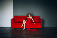Alluring woman sitting on red sofa