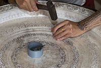Silversmith engraving a silver bowl with hammer and chisel, Ban Phanom, Laos