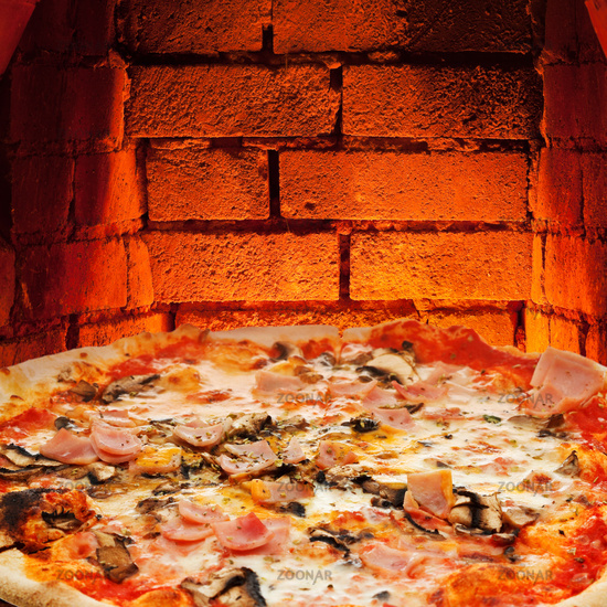 pizza with ham, mushroom and brick wall of oven
