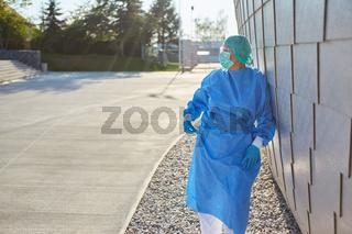 Arzt in Schutzkleidung macht Pause während Coronavirus Pandemie vor Klinik