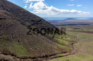 Panoramic view at landscape in the south of canary island Lanzarote with lava rocks and mountain in the foreground and the atlantic ocean in the background.