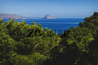 View to the rock of Calpe 'Ifach' over mediterranean sea and blurred pines at natural park 'Serra Gelada' in Albir, Spain