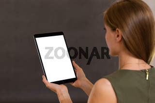 Alert female using tablet in vertical orientation and reading from white screen.
