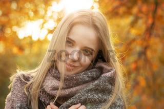 happy woman smiling in park at autumn sunset