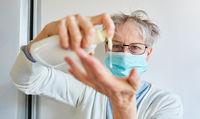 Seniorin macht flüssige Seife auf Hände wegen Coronavirus