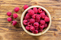 Full bowl of fresh ripe raspberries on wooden table