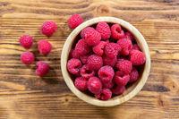 Full bowl of fresh ripe raspberries on wooden table