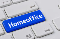 A keyboard with a blue button - Homeoffice