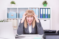 Businesswoman working frustrated indoors at home office. Work, communication and business concept.