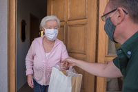 Senior woman with face mask gets shopping bag from neighborhood assistance