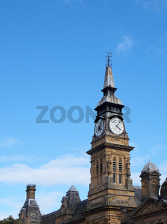the clock tower of the historic victorian atkinson building in southport merseyside against a blue summer sky