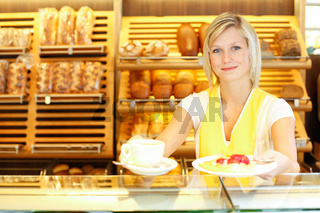 Shopkeeper in baker's shop preparing coffee and cake