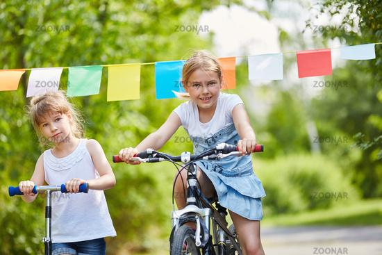 Kinder mit Fahrrad und Roller machen Rennen