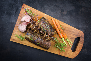 Barbecue rack of lamb with carrot and herbs offered as top view on a modern design wooden board with copy space