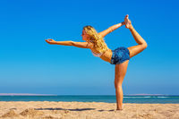 Young blonde woman in yoga position on beach