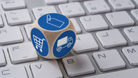 A die with icons on a keyboard - Online shopping
