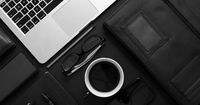 Business desktop concept. Mix of office supplies and gadgets on a black table background