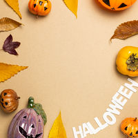 Halloween concept. Pumpkin and autumn leaves, sweet persimmon fruit on brown background. flat lay, top view, copy space
