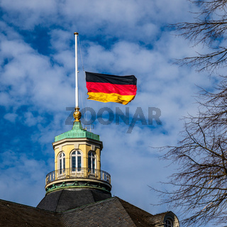 Close view on German Flag at Halfmast, auf Halbmast, on the tower roof of Castle Karlsruhe, blue sky behind. Germany.