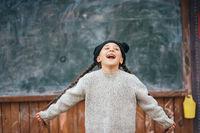 Little girl in a hat posing on the background of the school blackboard