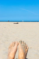 Bare foot on the sandy beach with blue sky