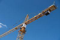Crane on construction site under blue sky - construction vehicle